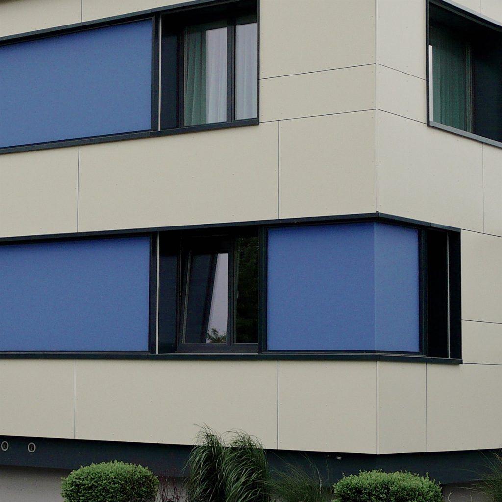 Ansicht Nordecke | Fensterbänder mit blauen Glas-Zwischenfeldern | Grossformat-Eternitplatten