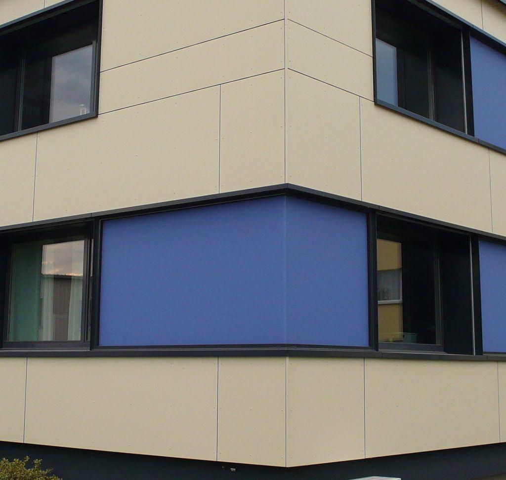 Ansicht Südecke | Fensterbänder mit blauen Glas-Zwischenfeldern | Grossformat-Eternitplatten